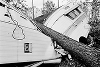 USA. Mississippi. Waveland. Aftermath of hurricane Katrina. Most houses were  destroyed by the storm, the tidal surge (water wave) and the floods. A trailer has been crushed by a fallen tree. The area is now empty and all its inhabitants have left away. The people could no longer and ever live again in the trailer. The entire area needs to be bulldozed before any new construction can be built. Household waste. Destruction of the urban american way of life.© 2005 Didier Ruef