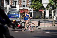 In Utrecht rijdt een jonge vrouw op de fiets met een klein kind in de aanhanger door de binnenstad..<br /> <br /> A young woman is cycling with a child in a trailer in downtown Utrecht.
