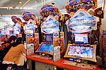 People playing Quiz Magic Academy slot machine at an arcade in Tokyo, Japan.