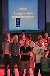 Nederland, Haaren, 03-09-2010 Dorpsbewoners luisteren naar presentatie van Frank de Boer directeur Cuadrilla. Achter hen wordt de tekst: Schaliegas is de beste toekomstige energiebron! geprojecteerd. De gemeente Haaren in Noord-Brabant organiseert een avond met film en debat op het dorpsplein. Ze willen de meningen peilen over het toestaan van boringen naar schaliegas. De Stichting SchalieGASvrij Haaren en het bedrijf Cuadrilla Resources spreken tijdens de manifestatie.  .FOTO: Gerard Til