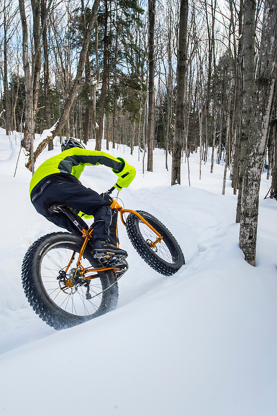 Winter cyclists on fat bikes ride the Noquemanon Trails Networks Snow Bike Route a groomed winter biking trail in Marquette, Michigan.