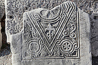 """Fragment of decorative Christian carving showing a diamond-shaped design with interlinked lines and floral and vegetal motifs, from the nave of the Basilica of St John, built 536-565 AD under Emperor Justinian on the site of the apostle's tomb, Ephesus, Izmir, Turkey. St John the Evangelist spent his last years in Ephesus and died here. In the 4th century a church was erected over his tomb but in the 6th century Justinian ordered the construction of a large, 6-domed basilica built of stone and brick with marble columns in a Greek cross plan, the ruins of which we see today. The church measures 130x56m and was an important Christian pilgrimage site, attaining the status of """"Church of the Cross"""". Originally, the church interior would have been covered with frescoes, and the vaults with mosaics. An earthquake in the 14th century destroyed most of the building. Ephesus was an ancient Greek city founded in the 10th century BC, and later a major Roman city, on the Ionian coast near present day Selcuk. Picture by Manuel Cohen"""