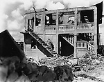 August 1944 - A member of the 3rd Maine Division searches for a sniper in a shelled building on Guam.