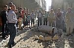 Syrians gather around unexploded barrel bomb, thrown by Syrian government forces in Bab al-Nairab district in the northern Syrian city of Aleppo, June 30, 2015. Photo by Ameer al-Halbi