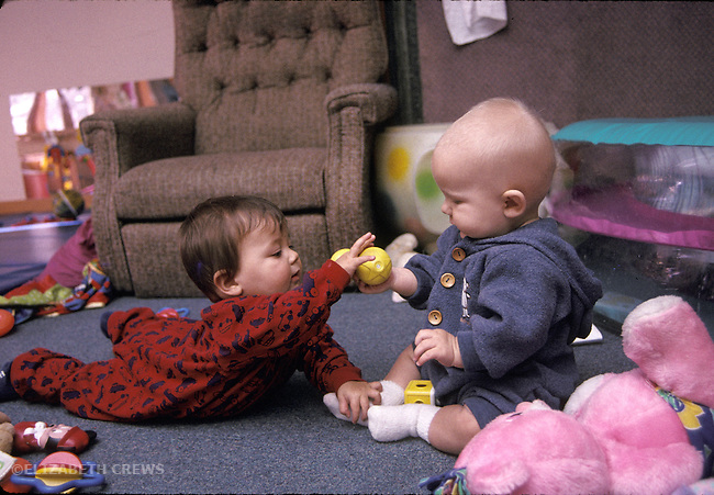 Berkeley CA Babies around ten-months-old sharing toy at day care