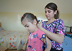 Lydia Nadar, 17, brushes the hair of her 4-year old sister Hilda in their apartment in Amman, Jordan. The girls' family, which is Christian, came to Amman as refugees from Mosul, Iraq, where the Islamic State had made threats against them. Along with another family--nine people in total--they are living in one crowded apartment, hoping for repatriation to a third country. The families received a box of household supplies from International Orthodox Christian Charities, a member of the ACT Alliance, which included a new hairbrush, which Lydia is using to brush Hilda's hair.<br /> <br /> Parental consent obtained.