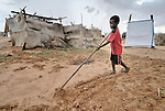 A boy prepares the soil next to his family's home for planting in the Dereig Camp for internally displaced persons, one of many such settlements for people displaced by the violence in Darfur.