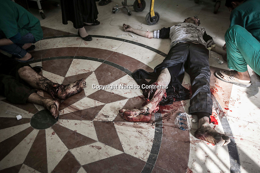 In this Tuesday, Oct. 23, 2012 photo. Syrian civilians get emergency medical attention at the lobby of one hospital in Tarik Al-Bab as they arrive badly injured after an attack by mortar shelling targeted one bakery in Hananu district, at the northeast of Aleppo City. (AP Photo/Narciso Contreras).