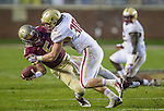 Florida State quarterback Jameis Winston passes as he is hit by Boston College linebacker Mike Strizak in the second half of an NCAA college football game in Tallahassee, Fla., Saturday, Nov. 22, 2014. Florida State defeated Boston College 20-17.  (AP Photo/Mark Wallheiser)