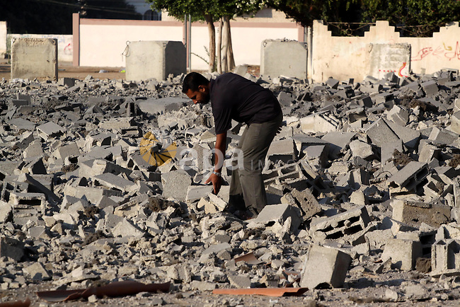 A Palestinian man stands past a damaged government building after an Israeli air strike in Gaza August 19, 2011. Israeli aircraft struck Hamas security installations in Gaza on Friday, killing at least one Palestinian, in further retaliation for attacks along the Egyptian border in which eight Israelis died. Photo by Mohammed Asad