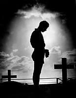 Silhouetted in the golden glory of a Pacific sunrise, crosses mark the graves of American boys who gave their lives to win a small atoll on the road to the Philippines.  A Coast Guardsman stands in silent reverence beside the resting place of a comrade.  1944. (Coast Guard)<br /> Exact Date Shot Unknown<br /> NARA FILE #:  026-G-3971<br /> WAR &amp; CONFLICT BOOK #:  1350