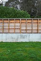 A concrete wall surmounted by a rustic fencing encloses the garden