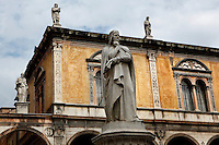 Low angle view of Statue of Dante Alighieri, 1865, by Ugo Zannoni, (1836-1919). Whilst exiled from Florence, the famous Italian poet, Dante, (1265-1321), lived in Verona. This monument was erected to commemorate the 600th anniversary of his birth. In the background statues of illustrious citizens of Verona crown the Loggia del Consiglio, 1476. Picture by Manuel Cohen.