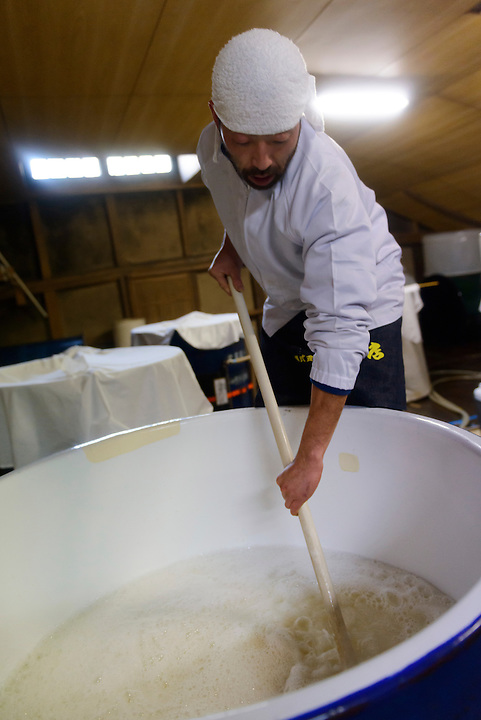 """Brewery worker stirring a sake starter. Tsuji Honten Sake, Katsuyama town, Okayama Prefecture, Japan, February 1, 2014. Tsuji Honten was founded in 1804 and has been at the cultural centre of the town of Katsuyama for over two centuries. 34-year-old Tsuji Soichiro is the 7th generation brewery owner. His elder sister, Tsuji Maiko, is the """"toji"""" master brewer."""