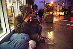 Jason, a teenage runaway, sits out of the rain with his dog begging for share change on Haight Street In San Francisco, California.  Jason has been homeless for seven years since he was 16-years-old.