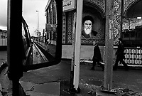 Ghaemshahr, Iran, March 28, 2007.Passers-by walk in front of a Revolution Guards building,  .A tile portrait of Imam Khomeiny gazing at his legacy....