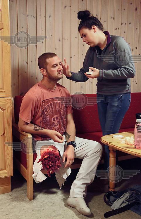 Devon Bishop helps Will Scott with make up before a medical exercise.  Both work with Amputees in Action, an agency offering professional amputee actors.