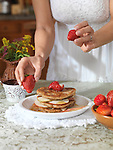 Closeup of a woman hands decorating a plate of pancakes with strawberries at home