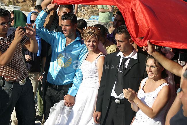 Two Palestinian couples under a big Palestinian flag participate in a protest against the controversial Israeli barrier before their wedding ceremony in the West Bank village of Maasarah, near Bethlehem, Friday, July 31, 2009. The couples said they were there as a creative form of protest to show how hard it is for Palestinians to move around and live in the West Bank. Photo by Najeh Hashlamoun