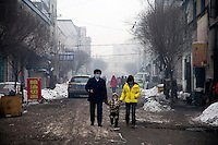 People walk through a Han neighborhood in Urumqi, Xinjiang, China. The city is divided between Han and Uighur ethnicities, and violent clashes erupted between the groups in 2009.