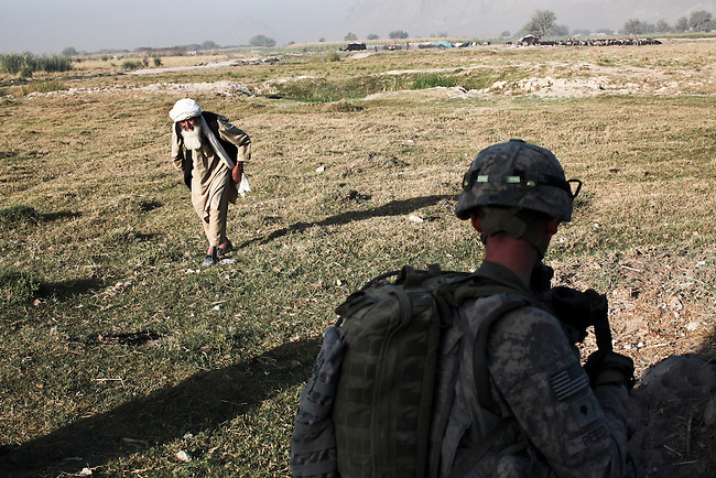 An elderly man approaches U.S. soldiers from Company D, 1st Battalion, 22nd Infantry Regiment who have stopped to chat with villagers while on patrol in Malajat, near Kandahar, Afghanistan. Oct. 9, 2010. DREW BROWN/STARS AND STRIPES
