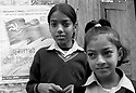 Two schoolgirls stand next a Maoist poster.