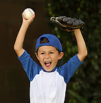 Young hispanic boy with baseball and glove celebrates on dark background