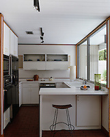 An old kitchen has been updated with white laminated units and a brick floor
