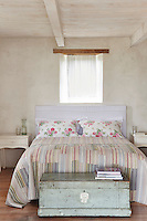 A white-washed country bedroom with a beamed ceiling and a plain curtain at a simple window. A double bed has a colourful striped cover and floral pattern cushions.