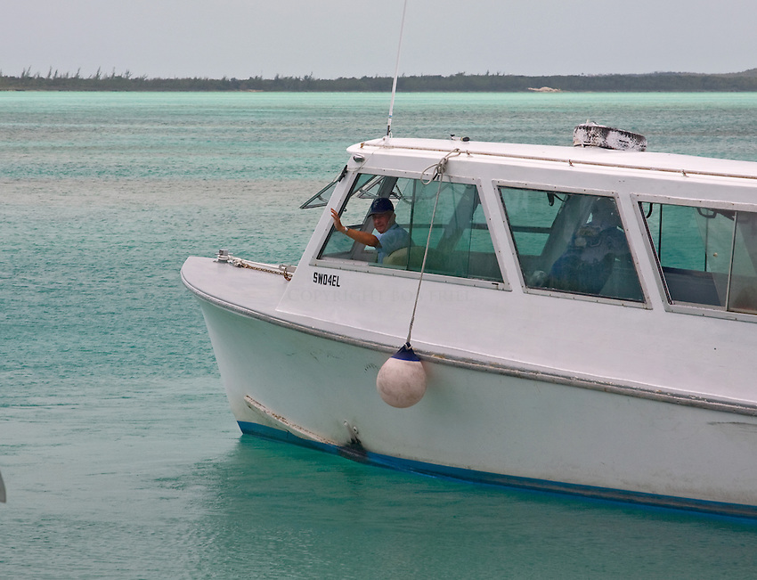 Captain of an Eleuthera water taxi waves as he leaves Eleuthera for the short trip across to Spanish Wells