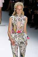 Hanne Gaby Odiele walks runway in a magenta psychedelic printed silk chiffon V-neck top with stretch cotton criss cross cutaway overlay and peplum belt, and magenta psychedelic printed stretch cotton skinny pant.by Vera Wang, for the Vera Wang Spring 2012 collection, during Mercedes-Benz Fashion Week Spring 2012.