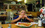 David Wells, 6, munches down a cheeseburger and fries while dining with his brother and dad at the Old Deschutes River Inn in Maupin, Oregon.