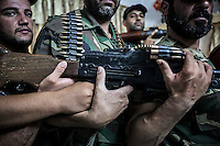 """Members of a rebel faction of the FSA at Ibeen town hold a machine gun inside a security house as they show the weaponry they have to protect the so called """"liberated territory""""."""
