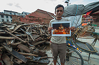 Nepal, Kathmandu, earthquake damage at Kathmandu Durbar Square. Man holding my photo of how the temples looked previously.
