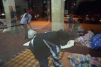 Italy. Lombardy Region. Como. Homeless african migrants sleep at night in the San Giovanni railway station. Ethiopian women lay blankets on the ground for the night. A Italian policeman is standing close to a pillar. 10.08.2016 © 2016 Didier Ruef