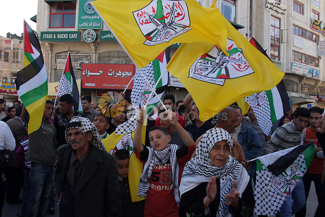Palestinian Fatah supporters wave the party's flag and hold a picture of Palestinian leader Mahmud Abbas during a protest against his decision to not seek re-election in in the West Bank city of Ramallah on November 6, 2009. Abbas said he did not want to stand for a new term in January elections as he voiced frustration with the US position on Israeli settlements and delivered a major blow to Washington's Middle East peace efforts. Photo by Issam Rimawi