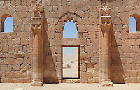 Internal wall of Qasr al Hallabat, with doorway, arched windows, pilasters topped with capitals and a view of the desert beyond, Jordan. This Umayyad palace complex was built on the site of a Roman fortress by Hisham ibn Abd al-Malik. The complex includes a mosque, water system and reservoir, irrigated agricultural land and the palace. The nearby bathhouse Hammam as Sarah served this desert castle. The building was originally decorated with mosaics, frescoes and stucco carvings. Picture by Manuel Cohen