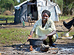 A woman cooks food over an open fire in the Gendrassa refugee camp in South Sudan's Upper Nile State. More than 110,000 refugees were living in four camps in Maban County in October 2012, but officials expected more would arrive once the rainy season ended and people could cross rivers that block the routes from Sudan's Blue Nile area, where Sudanese military has been bombing civilian populations as part of its response to a local insurgency. Conditions in the camps are often grim, with outbreaks of diseases such as Hepatitis E.