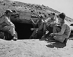 "Marine pilots of the little ""Grasshopper"" observation planes onat Yontan airfield on Okinawa have a sign over the entrance to their bomb shelter which tells how rapidly they take cover when it is necessary. From left: 2nd Lt. Donald H. Rusling, Capt. Donald R. Garrett, 2nd Lt. Lester E. Bartels and 2nd Lt. Glenn R. Hunter."