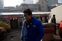 Workers walk through a wholesale market in Urumqi, Xinjiang, China.