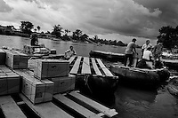 Boxes of smuggled goods are loaded on the inner tube rafts anchored on the shore of the Suchiate river in Tecún Umán, Guatemala, 23 May 2011. Having no migration or commercial controls, the Suchiate river serves as an illegal crossing point between the southern Mexican state of Chiapas and Guatemala. Every day, hundreds of people from both countries, crossing the river on the unstable rafts called ?camaras?, smuggle soft drinks, toilet papers, fruits, vegetables and other supplies. The river crossing is also widely used by the Central America immigrants heading to the north, to the United States, in the search of better life.