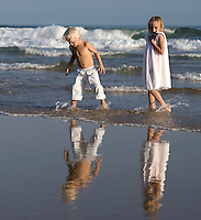 Two children walk in the shallow waters along the shoreline