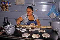 Woman cooking cooking pupusas in a pupuseria, San Salvador, El Salvador