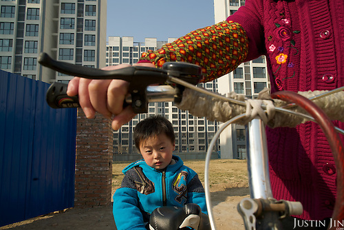 A former farmer transports her son on a bicycle inside a &quot;replacement housing block&quot; in Hebei province, just outside Beijing, built for people like her who has lost their farmland to a new phase of state-driven urbanisation. Because of the speed of the construction roll-out across China, they follow mostly the same blueprint. <br /> <br /> For generations, Chinese farmers picked vegetables on family plots in China, a mainly agrarian society right up until the 20th century.<br /> <br />  <br /> <br /> Faced with slowing exports, Communist leaders are pushing ahead with a historic plan to move 100 million rural residents into towns and cities by 2020 to create a new middle class and boost demand.<br /> <br />  <br /> <br /> As a non-resident Chinese, Justin views the situation both as a concerned citizen and a questioning outsider. As he crisscrosses the country talking with farmers, he gets a feeling the government&rsquo;s maths might be right, but wonders at the long-term consequences for society.<br /> <br />  <br /> <br /> What happens to humanity -- and the earth -- when millions of subsistence farmers clamor to join the consumptive middle class in half a decade?<br /> <br />  <br /> <br /> This series for Sony is shot in Hebei province, just outside Beijing, as part of his bigger project.