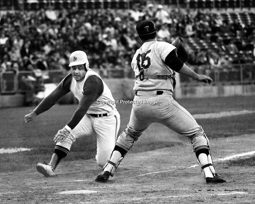 Oakland Athletics third baseman Sal Bando avoids the tag of Minnesota Twins catcher #15 to score run for the A's. (1970 photo/Ron Riesterer)
