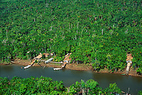 Aerial of riverside houses with rainforest in background in Amazon Tocantins estuary complex Para Brazil