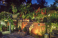 Night lighting in small backyard urban garden patio with steps and brick retaining wall, San Francisco