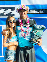 PIPELINE, Oahu/Hawaii (Saturday, December 14, 2013) Kelly Slater (USA) with his girlfriend Kalani Miller (USA).- Kelly Slater (USA), 41, has won his 7th Billabong Pipe Masters in Memory of Andy Irons after a day of incredible 10-to-15 foot (three to four metre) waves at Pipeline today. Slater defeated John John Florence (HAW), 21, in a hard-fought, 35-minute Final that ended with less than half-a-point separating the two. The runner-up finish for Florence saw him crowned 2013 Vans Triple Crown of Surfing champion.<br /> <br /> The final day of the Billabong Pipe Masters capped off the 2013 ASP World Championship Tour (WCT) season in fine style, with epic conditions providing the ideal backdrop for the crowning of Mick Fanning (AUS), 32, as the ASP World Champion. It also finalized the ASP Top 34 roster for 2014. Fanning finished third overall, defeated by Florence in their Semifinal.<br /> With tens of thousands packing the beach at Pipeline, and the gravitas of Slater&rsquo;s 56th elite tour victory apparent, the greatest athlete the sport has ever produced was emotional on the final day of 2013.<br /> <br /> Fanning&rsquo;s road to the 2013 ASP World Title was nothing short of spectacular on the final day of competition. Finding himself behind during both his Round 5 and Quarterfinals bouts, the iron-nerved Australian nailed huge Pipeline scores in both occasions to take the heat wins and his third world surfing crown.<br /> <br /> &ldquo;I&rsquo;ve never put myself in the same circles as Tom Curren and Andy Irons,&rdquo; Fanning said. &ldquo;Tom (Curren) is such an enigma and was so instrumental to injecting style into our sport. Andy (Irons)&hellip;what hasn&rsquo;t been said about Andy? He was such a legend and he was such a good friend. I&rsquo;m honored to be a part of this group. I was happy with one title and I was overwhelmed with two. With three? I don&rsquo;t have words for that.&rdquo;<br /> <br /> Today marked John John Florence&rsquo;s second Vans Triple Crown Title, but his runner-up in the final event forces him to hang on to his life-long dream of o
