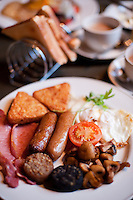Fried Irish Breakfast with black and white pudding, mushrooms, bacon, sausages, tomato, egg, and toast.