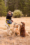 Woman giving treats to her dogs on Sagehen Creek trail, Tahoe National Forest California